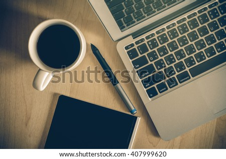 Top view of Laptop, notepad and coffee cup on office wooden background,flat lay