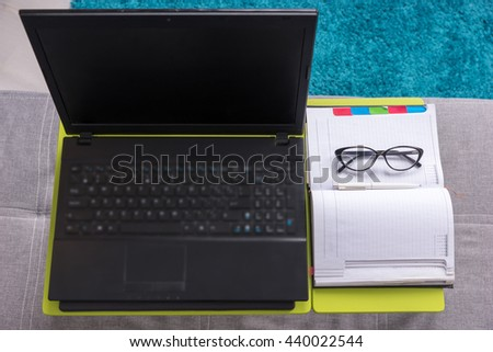 Top view of laptop table with laptop, diary, glasses and pen are arranged in strict order on it in living room - stock photo