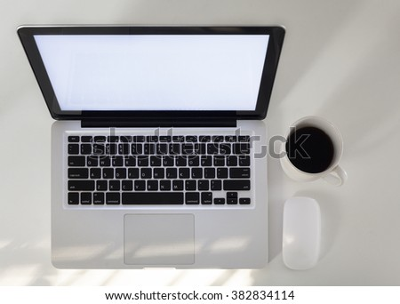 Top view of laptop with coffee on office table