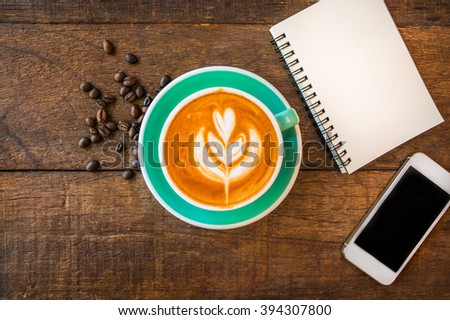 Top view of latte hot coffee, white smart phone and blank note book in coffee shop. Wooden table background. - stock photo