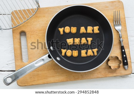 Top view of letter collage made of biscuits. Quote YOU ARE WHAT YOU EAT in frying pan. Other cooking equipments: fork, cookie cutter and chopping board putting on white wood table, vintage style. - stock photo