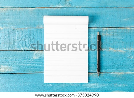 Top view of Lined note paper with pencil on blue wood table for background - stock photo
