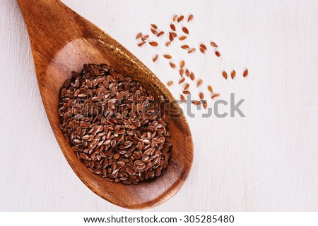 Top view of linseed in a wooden spoon over white wooden background. Close up image with copy space - stock photo