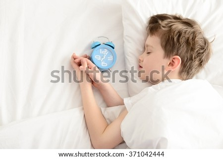 Top view of little boy sleeping in white bed with alarm clock near his head.  Sleeping boy. Sleeping child - stock photo