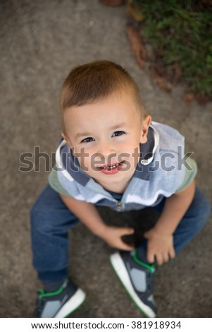 Top view of little boy standing on street looking up at camera.