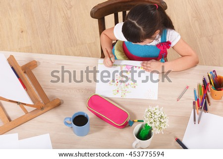 Top view of little girl sitting at table and drawing picture while sitting at table. Little lady using multicoloured pencils for drawing. - stock photo