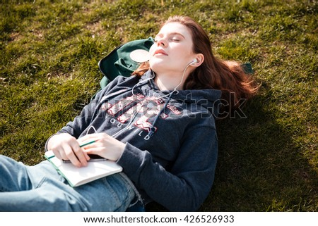 Top view of lovely relaxed young woman lying on the lawn with eyes closed and listening to music