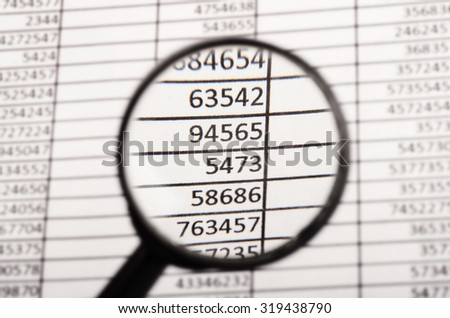 Top view of magnifying glass looking at financial report - stock photo