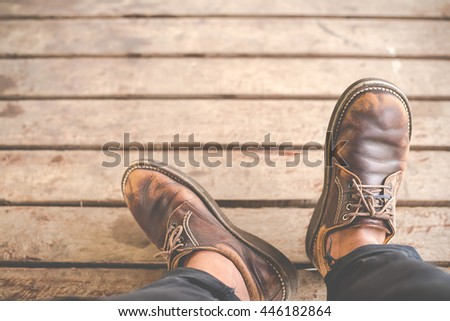 Top view of Male feet in old leather shoes on wood - stock photo