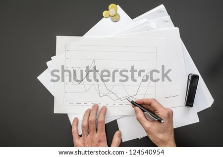 Top view of male hand holding a pen over a business document. - stock photo
