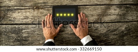 Top view of male hand holding digital tablet with five golden stars appearing on the screen. Conceptual of service and product ranking. - stock photo