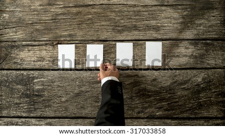 Top view of male hand in elegant business suit placing four blank white cards in a row on a rustic textured wooden boards. With copy space ready for your text or promotion. - stock photo