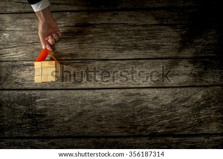 Top view of male hand placing a paper roof on top of a house made of many wooden blocks sitting on a textured rustic wooden boards with copy space on the right side. - stock photo