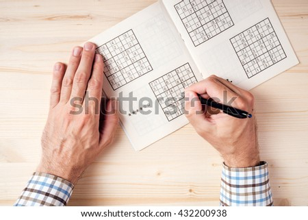 Top view of male hands solving sudoku puzzle on wooden office desk - stock photo