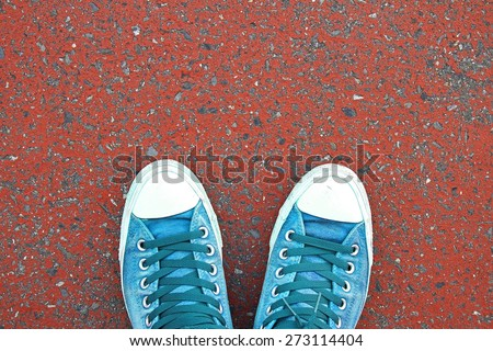 Top view of male sneakers on red concrete pavement. - stock photo