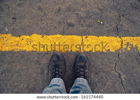 Top View of Male sneakers on the asphalt road behind yellow line. Border line concept, danger or warning sign at the frontier - stock photo