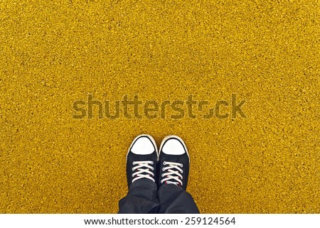Top View of Man standing at yellow asphalt pavement, sneakers from above, urban lifestyle concept with ground as copy space. - stock photo