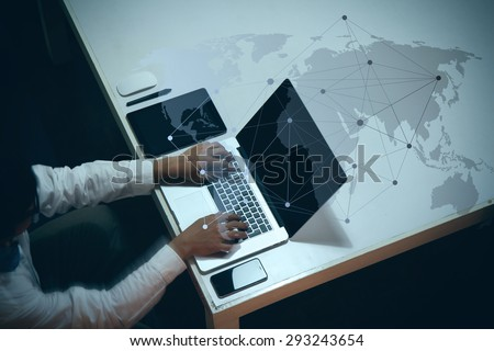 top view of man working with business documents on office table with digital tablet and man working with smart laptop computer with social media diagram - stock photo