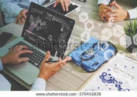 top view of Medicine doctor hand working with modern computer and digital pro tablet with his team with digital medical diagram on wooden desk as medical concept                                - stock photo