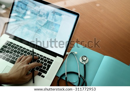 top view of Medicine doctor hand working with modern computer and smart phone on wooden desk as medical concept