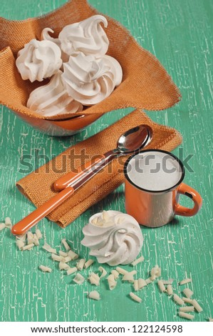 Top view of meringue, orange mug with milk foam, two spoons on textile napkin on green cracked background - stock photo