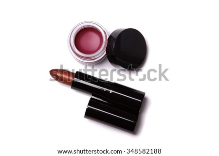 Top view of metallic red lipstick and lip gloss in jar, isolated on white background  - stock photo
