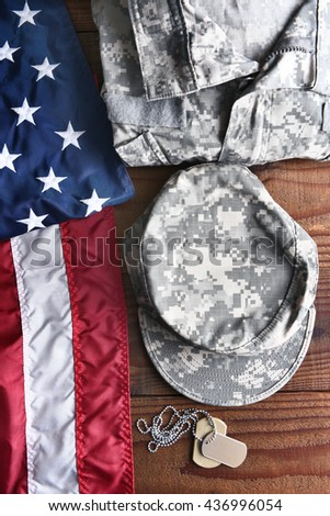 Top view of military fatigues, dog tags and American Flag on a wood background. Armed forces service concept for Memorial Day, Veterans Day and Patriotic events. - stock photo