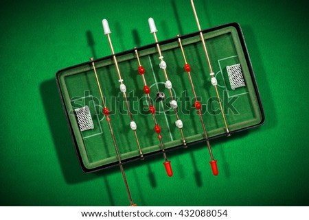 Top view of mini table football game with an old black and white soccer ball. On a green background with shadows - stock photo