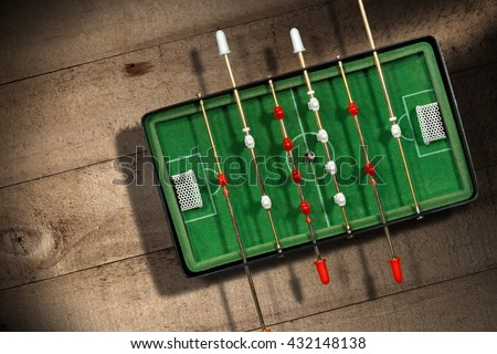 Top view of mini table football game with an old black and white soccer ball. On a wooden table with shadows - stock photo