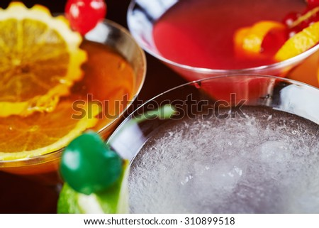 top view of mix bright delicious cocktail with decoration of pieces of orange and a cherry on the table in the restaurant with backgrounds from the disco light. beautiful bokeh and soft focus. - stock photo