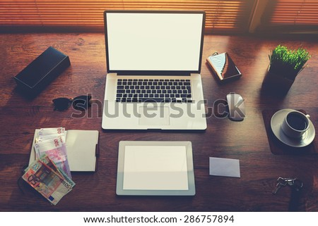 Top view of modern businessman or entrepreneur table with style accessories and euro bills, open laptop computer and digital tablet with white blank copy space screen for text information or content - stock photo