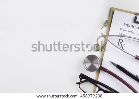 Top view of modern, sterile doctors office desk. Medical accessories on a white background with copy space around products.Workplace of a doctor. Stethoscope, clip board, glasses and other things