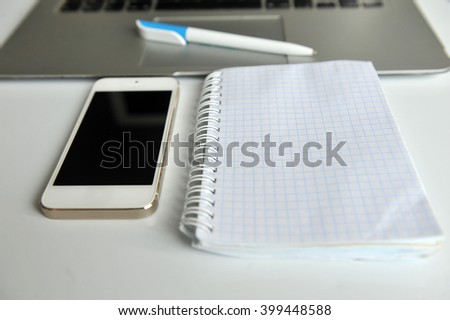 Top view of modern wood office table with laptop, smartphone, notebook and pen. Top view with copy space. - stock photo