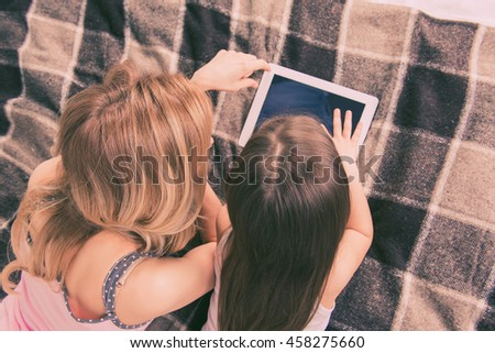 Top view of mom and daughter lying on bed and playing with tablet