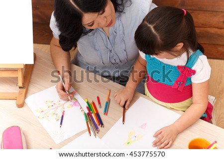 Top view of mother and her little daughter drawing pictures with multicoloured pencils while sitting at table at home.