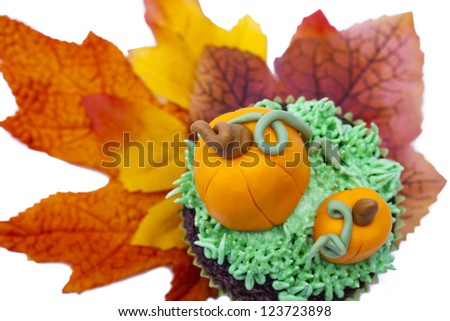 Top view of muffin decorated with pumpkin miniature and autumn leaves. - stock photo
