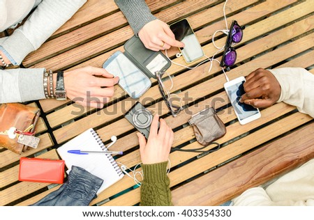 Top view of multiracial friends using smartphone on bar table. Social moment concept with men and women hands on mobile phones from above. Group of people are sitting and using technological devices. - stock photo