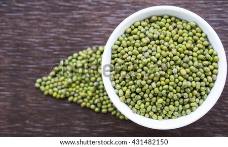 Top view of mung beans in white bowl on wooden background.