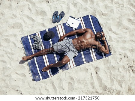 Top view of muscular young man sunbathing on beach. African guy wearing sunglasses and listening to music on headphones lying on a beach mat - stock photo