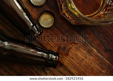 Top view of near empty beer glass with bottle caps and bottles on rustic wood background. Low key still life with directional natural lighting for effect. Selective focus on bottle caps and droplets.
