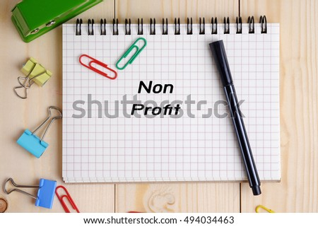Top view of Non profit on  notebook on wood table background concept. Decorated and blank space.