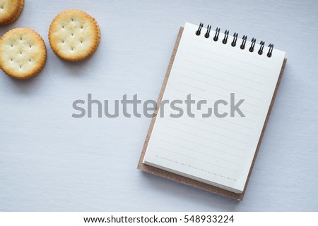 Top view of notepad and biscuits on table background.
