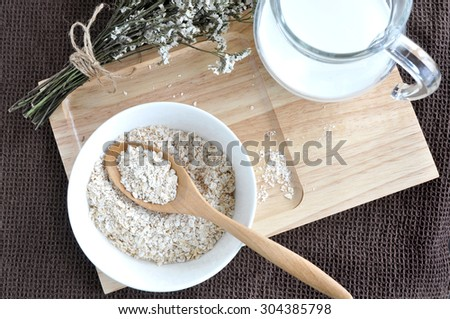 top view of oatmeal for breakfast on wooden tray put on brown fabric background - stock photo