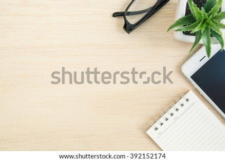 Top view of office desk table with mobile phone, spiral notebook, black glasses, and small tree in a white pot on wood table - stock photo