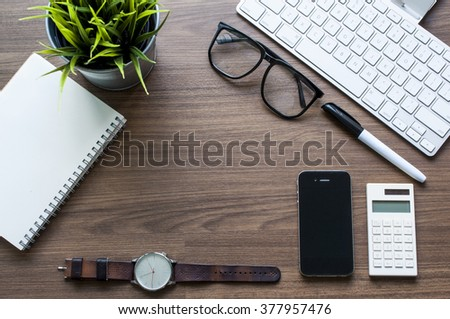 Top View Of Office Desk With Keyboard,small Green Flower ,smart Phone,watch