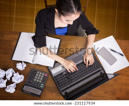 Top view of office desk with working women - stock photo