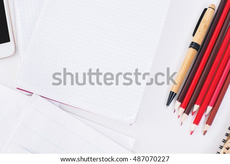 Top view of office desktop with blank notepad, colorful pencils and other items. Mock up
