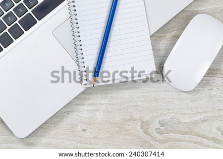 Top view of office wooden desktop with computer laptop, notepad, pencil and mouse.  - stock photo