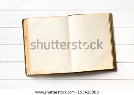 top view of old open book on white wooden background - stock photo