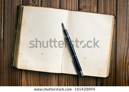 top view of old open book with fountain pen on wooden table - stock photo